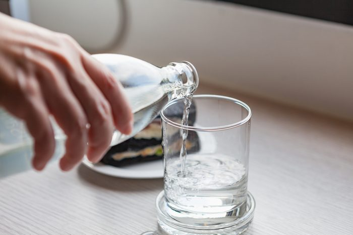 Drinking water is poured from a bottle into a glass on wooden table at office room.