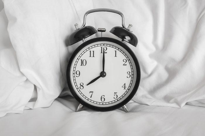 Still life with vintage alarm clock on bed ( alarm clock show 8 o`clock )