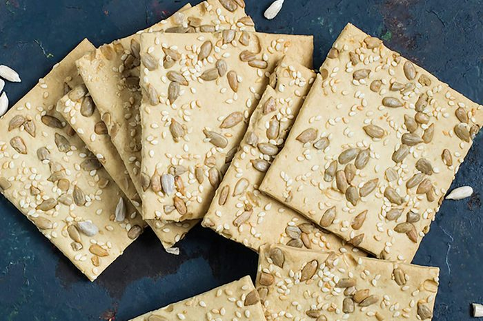 Homemade wholegrain crackers with sunflower seeds and sesame on the old blue textured background. The concept of diet and healthy eating. Top view