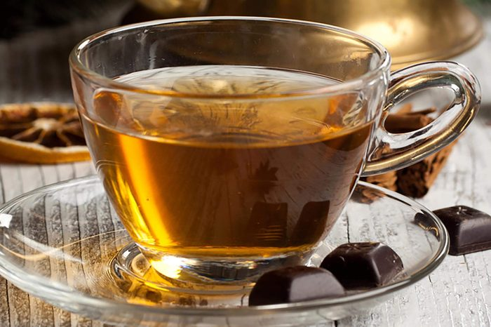 Cup of hot tea with dark chocolate on old wooden table