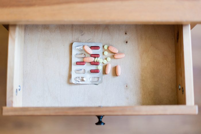 top view of pile of pills in open drawer of nightstand