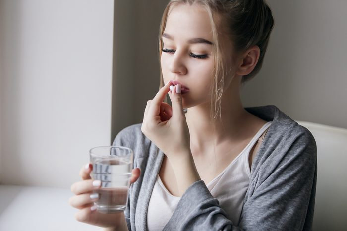 Young beautiful girl or woman to take a pill with a glass of water near the window in white shirt and grey robe