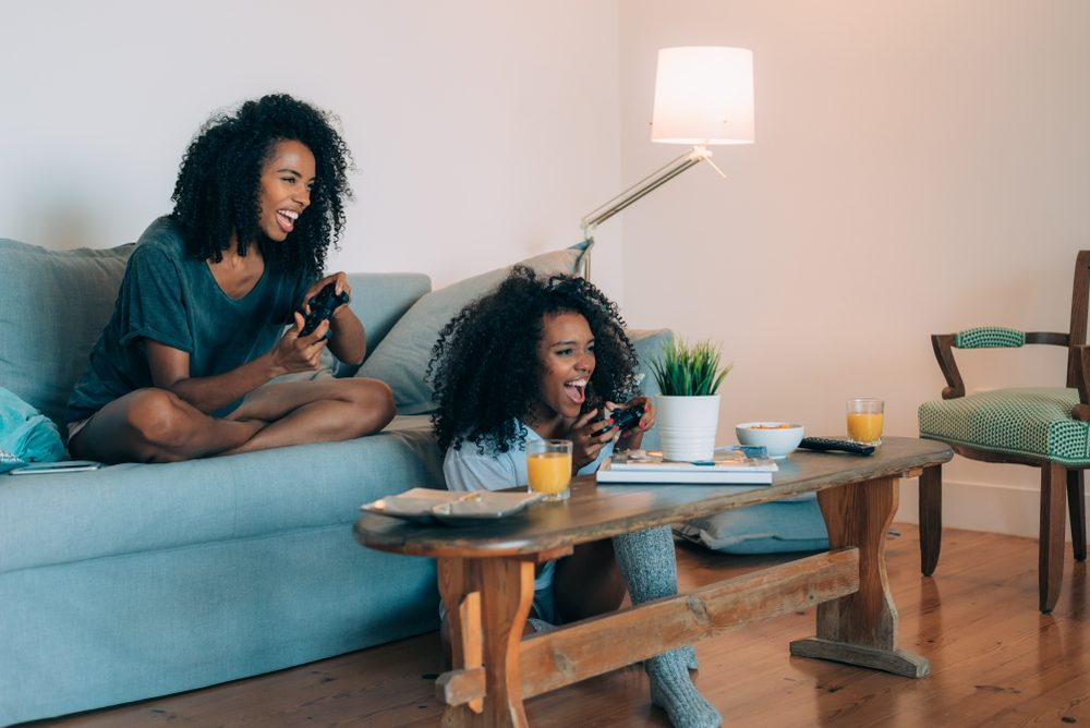 Happy young two black women sitting in the couch playing video games