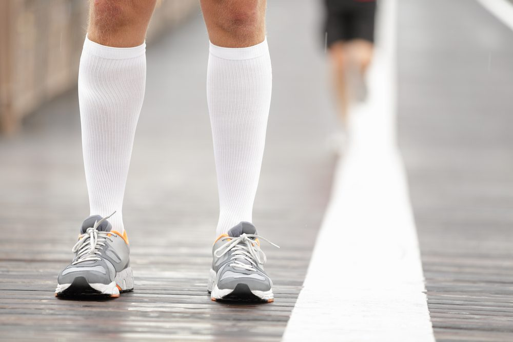 Running shoes closeup and compression socks on male runner. Closeup of runners feet on Brooklyn Bridge, New York City.