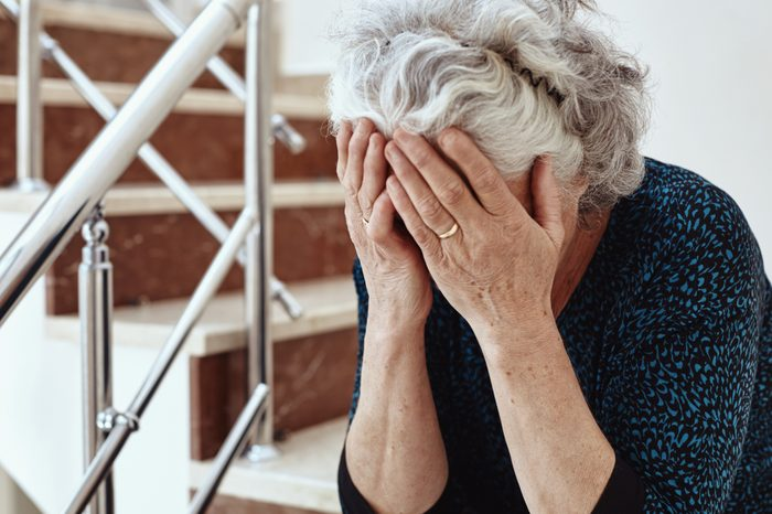 senior woman crying with head in hands
