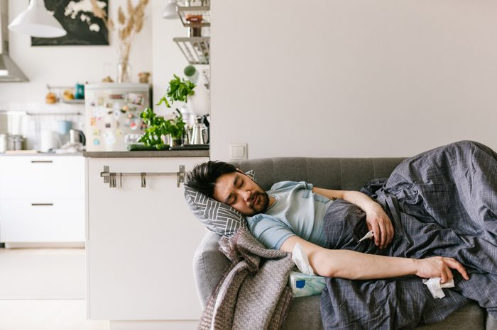 man sick with a cold on the couch