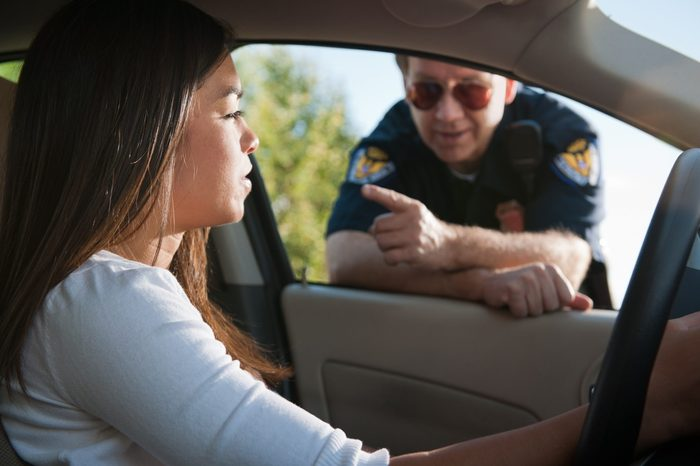 police officer talking to young woman pulled over