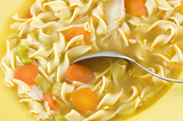 Homemade chicken noodle soup with carrots and celery in a yellow bowl, macro with copy space