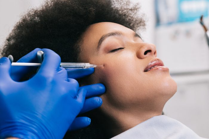 Anti-Aging Treatments   Attractive young African woman is getting a rejuvenating facial injections. She is sitting calmly at clinic. The expert beautician is filling female wrinkles by hyaluronic acid.