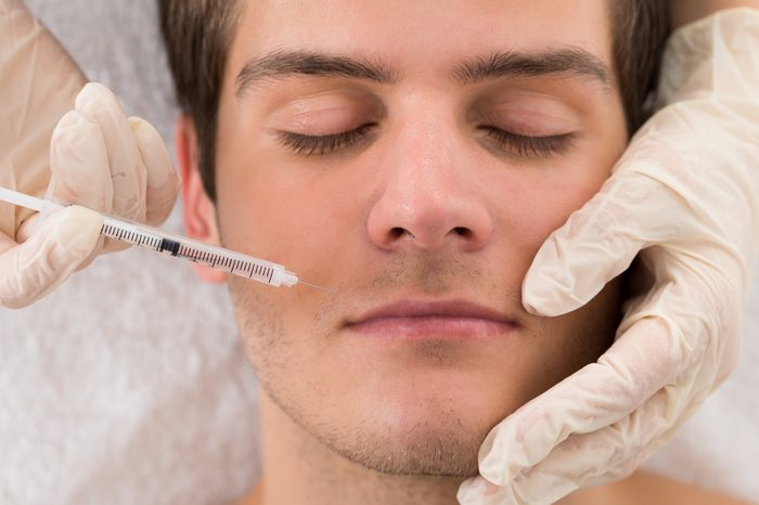Anti-Aging Treatments   Close-up Of Doctor In Glove Giving Injection On Face Of Man In Clinic