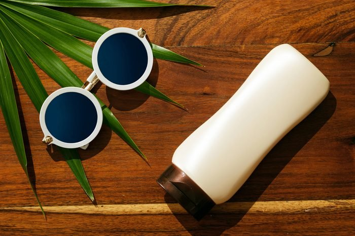 Different items for beach vacations. Sunscreen, sunglasses on wooden surface