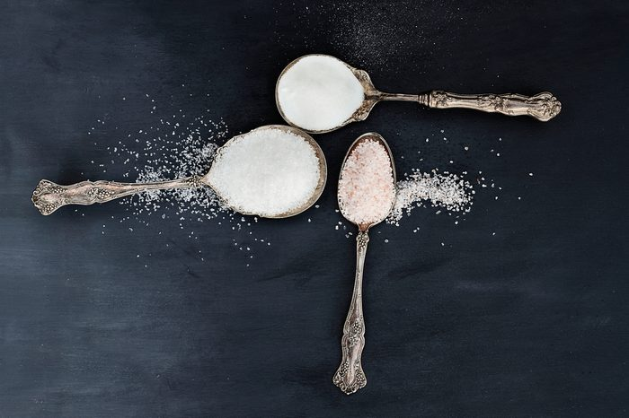 Three antique silver spoons filled with a variety of salts, Pink Himalayan, Sea Salt and table salt.