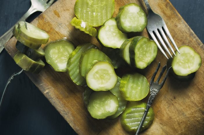 Overhead view of a bunch of pickle chips on a rustic cutting board with antique forks.