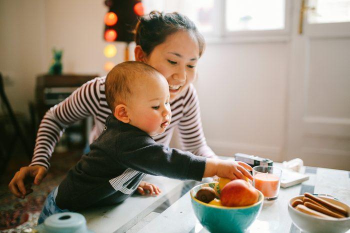 Gluten-free Diet   Celiac Disease   Gluten sensitivity   Gluten Intolerance   Baby reaching for fruit with mother in kitchen