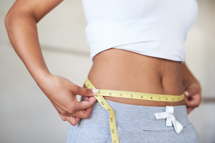 Gluten-free Diet   Celiac Disease   Gluten sensitivity   Gluten Intolerance   Woman measuring her waist in the bathroom