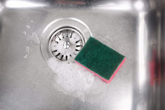 Stainless steel kitchen sink with soap suds and cleaning sponge