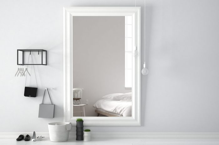 Scandinavian entrance lobby hall with mirror reflecting bright bedroom with bed, chair and table lamp, minimalist white interior design