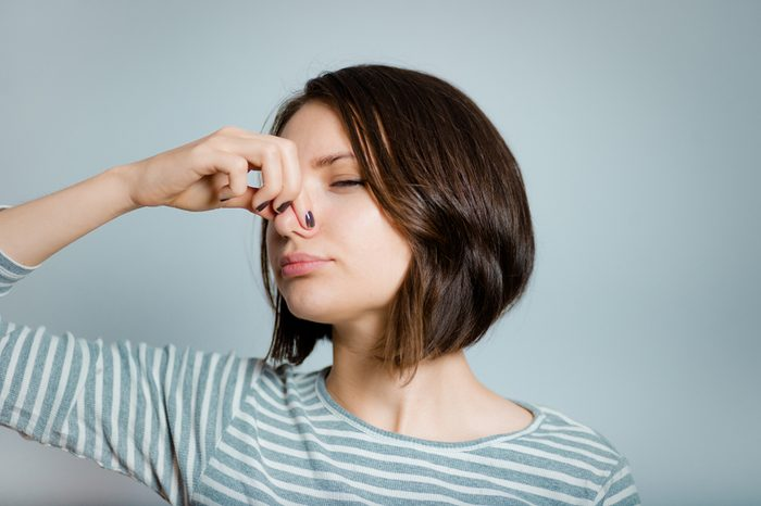 beautiful young woman closes nose because of a bad smell, isolated on background, studio photo