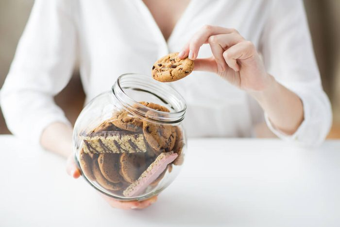 woman holding glass jar of cookies