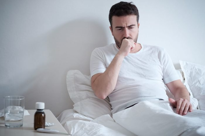 Man feeling bad lying in the bed and coughing