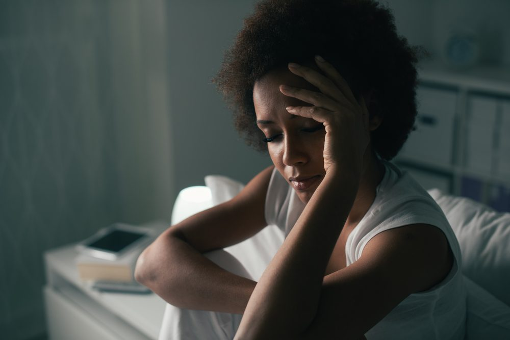 Wake up in the middle of the night | Sad depressed woman suffering from insomnia, she is sitting in bed and touching her forehead, sleep disorder and stress concept