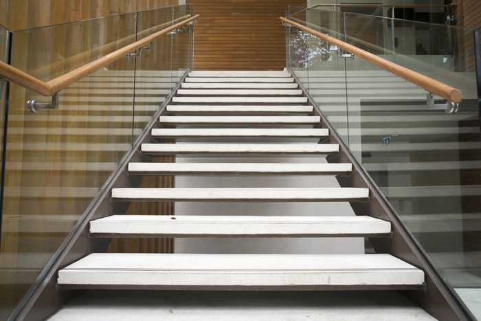 Modern white stairs with wooden handrail