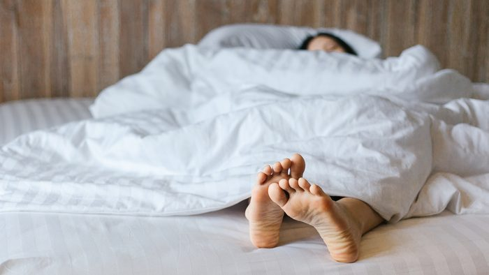 Fibromyalgia | Female feet under blanket flat lay. Female beautiful feet on the bed. Sleeping woman legs under white blanket
