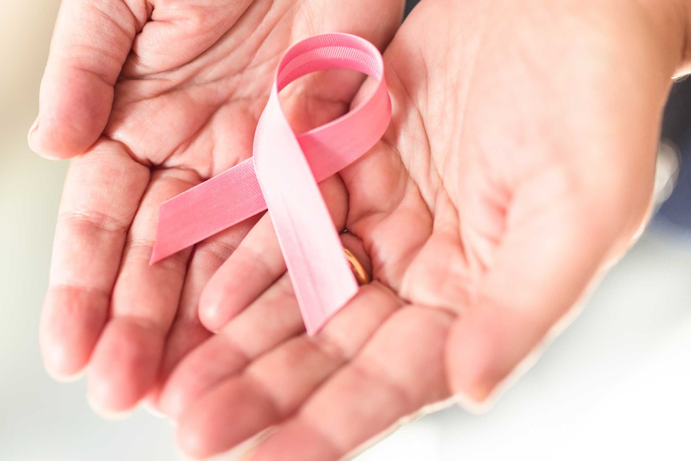 health myths gynecologists hear | hands holding pink breast cancer ribbon