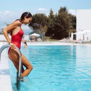 woman getting into swimming pool from ladder  catch coronavirus from swimming