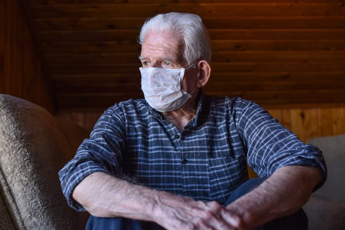 2020 | Portrait of senior man with respiratory mask looking outside from home window during quarantine