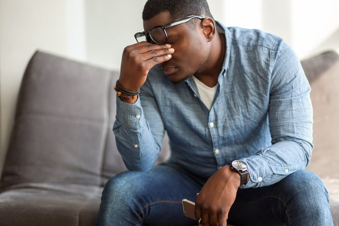Feeling exhausted. Frustrated young black man massaging his nose and keeping eyes closed while sitting at his working place in office