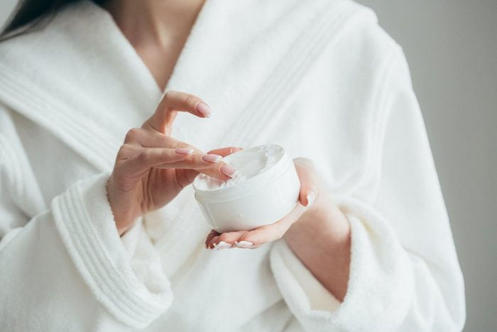 beauty products | Beautiful groomed woman's hands holding a cream jar on the fluffy blanket. Moisturizing cream for clean and soft skin in winter time. Manicure beauty salon. Healthcare concept. Spa