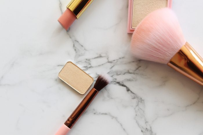 shouldn't be stored in the bathroom   Gold and pink makeup objects against white marble copy space.