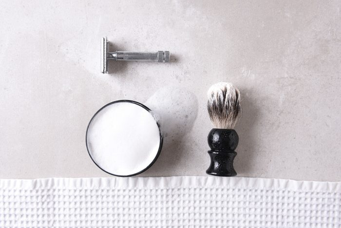 shouldn't be stored in the bathroom   Shaving Still Life: Safety razor with towel, brush and soap on a gray tile surface.