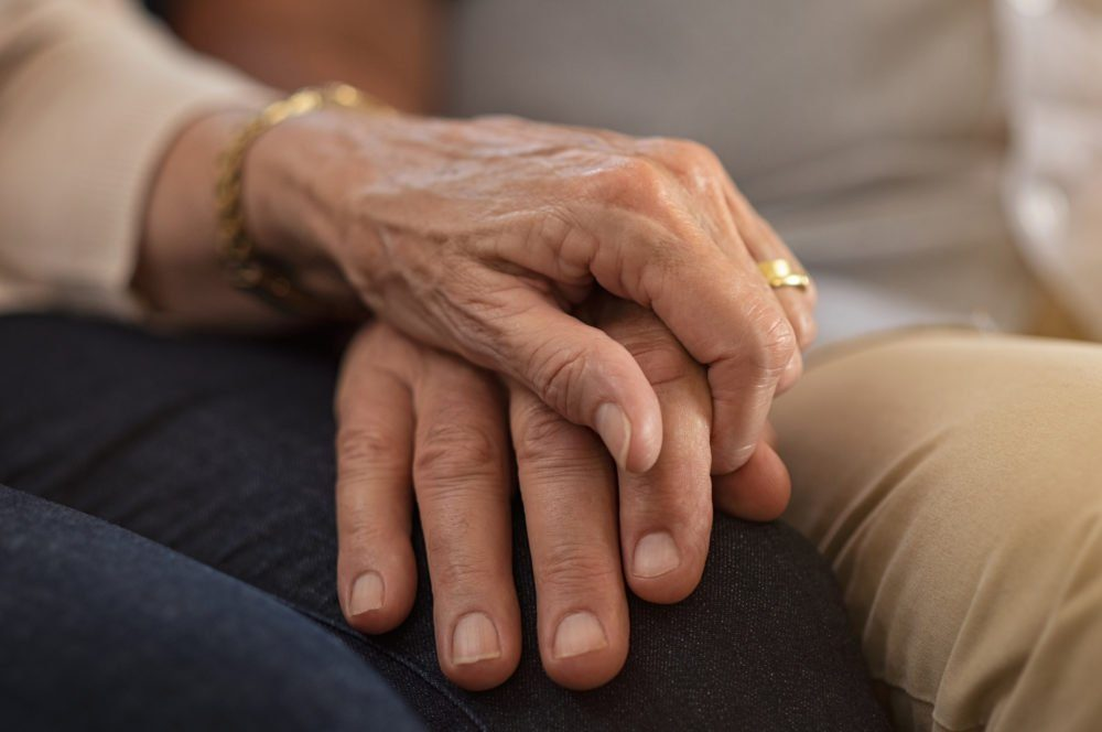 early-onset Alzheimer's | elderly couple holding hands comforting each other