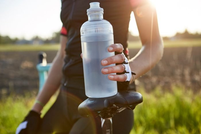 situations that cause dehydration   close up of cyclist holding water bottle