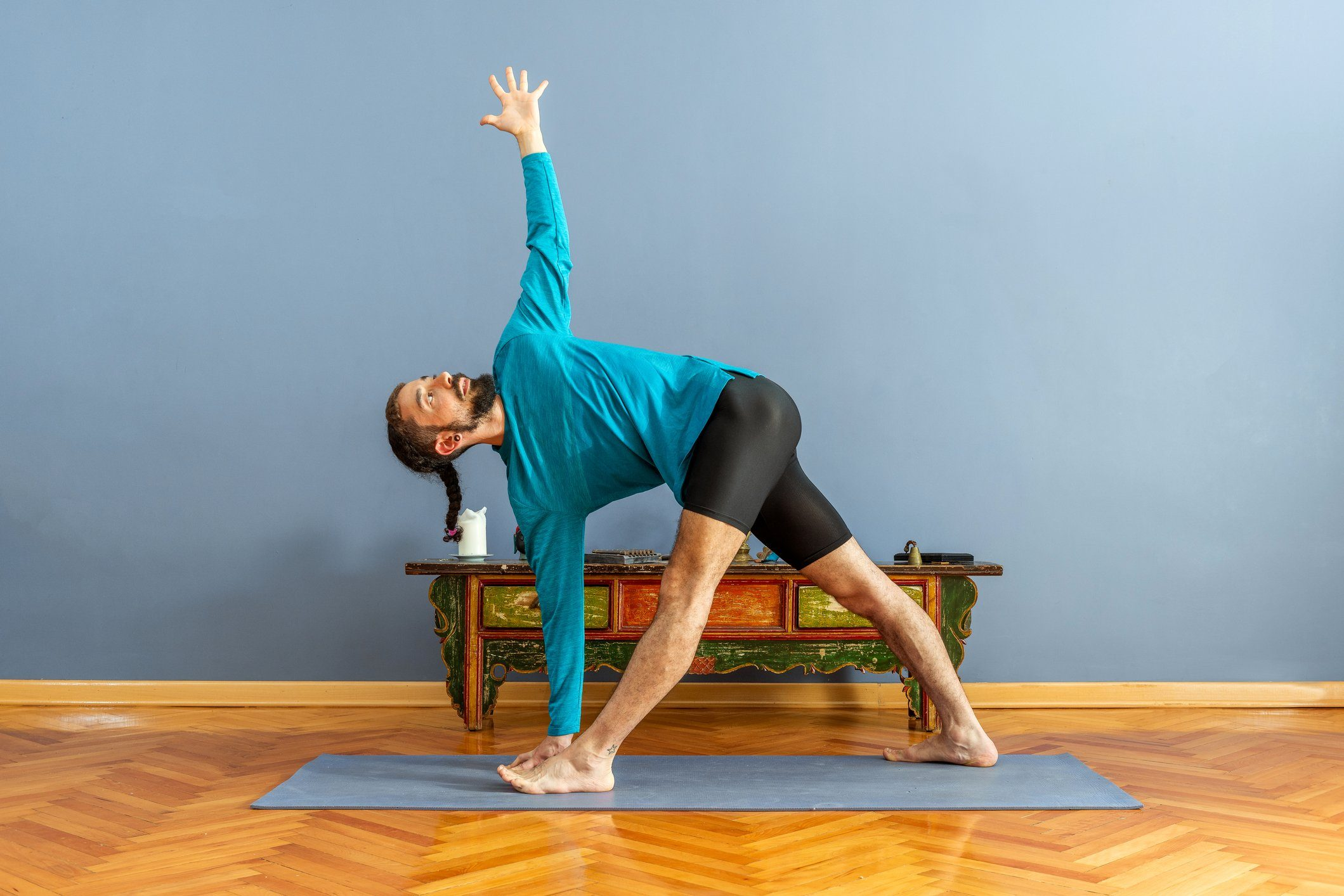 man doing revolved triangle yoga pose
