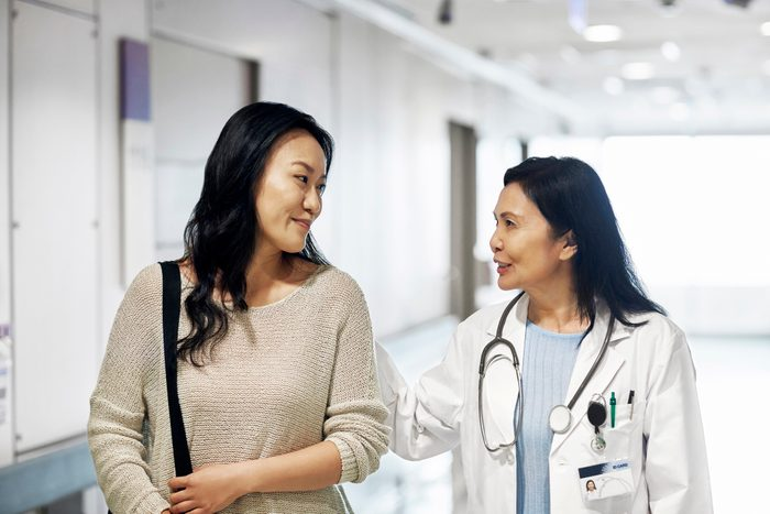 woman talking with doctor while walking