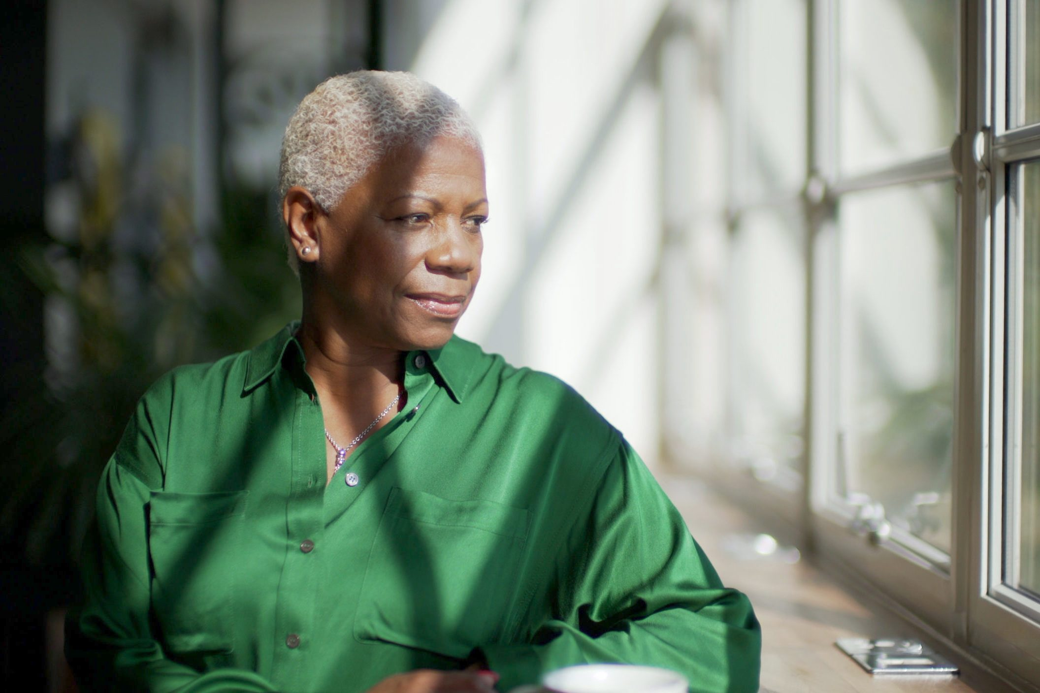 early-onset Alzheimer's | mature woman sitting at home looking out the window