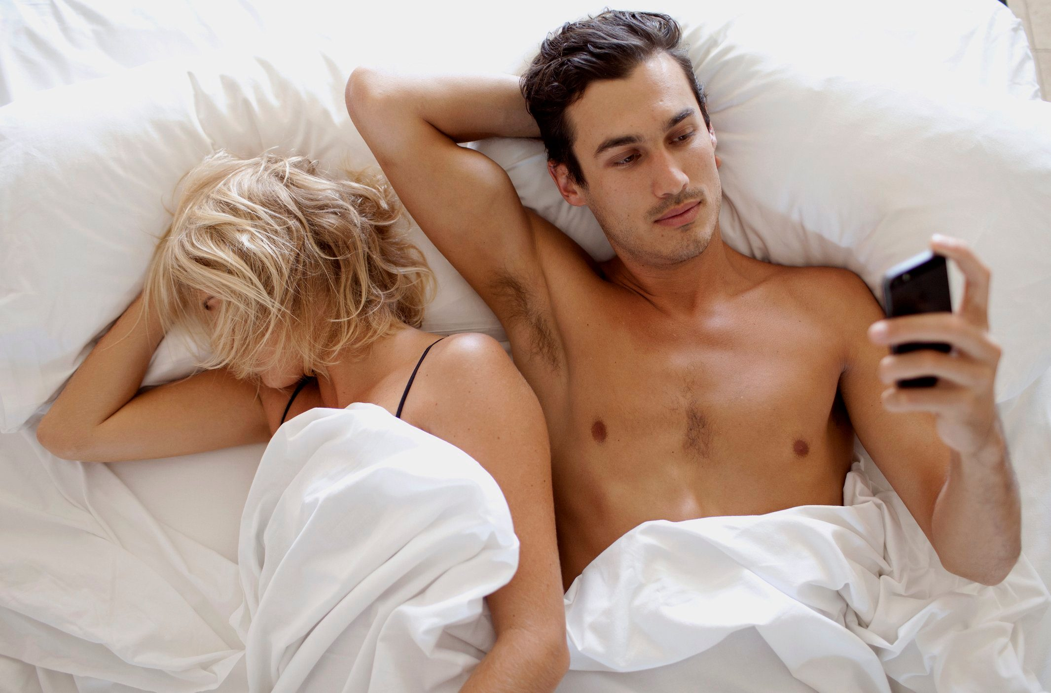 sex mistakes | man looking at phone in bed with woman