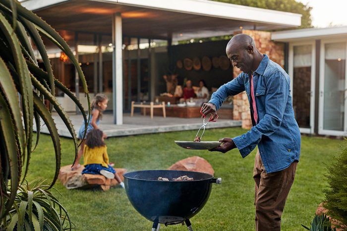 healthier grilling | man grilling in his backyard with family