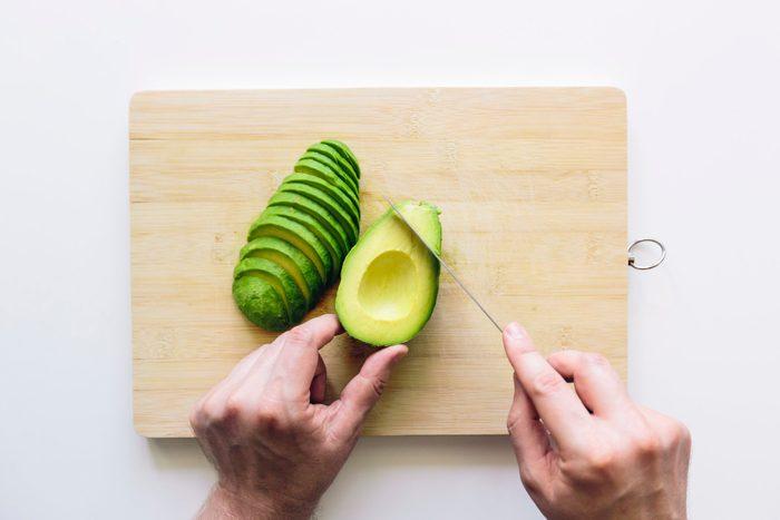 overhead shot of man slicing avocado