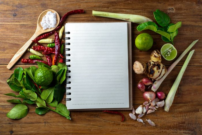 reach your goal weight | recipe book with fresh herbs south asia and spices on wooden background, thai food.