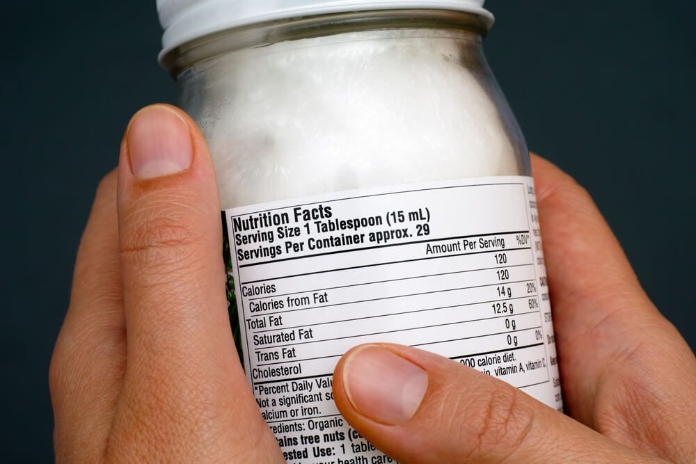 reach your goal weight | Reading a nutrition facts on organic coconut oil jar. Close-up.