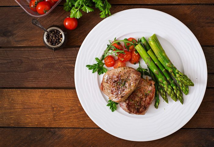 reach your goal weight | Barbecue grilled beef steak meat with asparagus and tomatoes. Top view