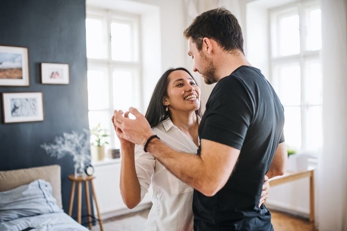 couple dancing at home together smiling
