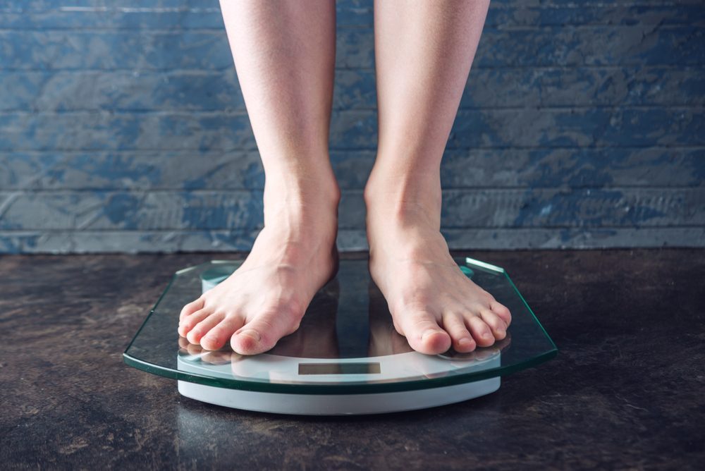 Female feet standing on electronic scales for weight control on dark background. The concept of sports training, diets and weight loss