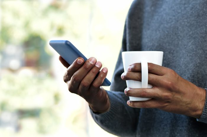 nomophobia   close up of person holding coffee mug and smartphone