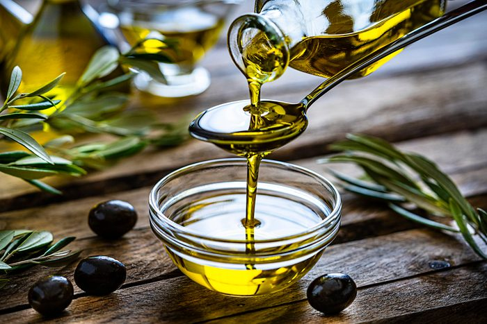 mediterranean diet   pouring extra virgin olive oil in a glass bowl