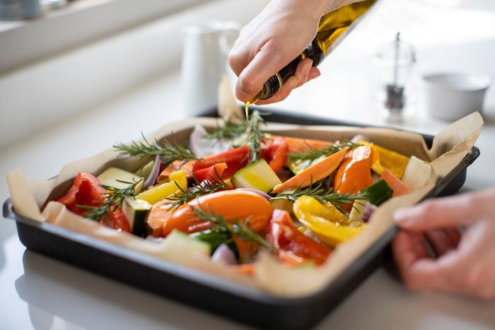 healthiest cooking oils | drizzling olive oil on pan of vegetables